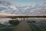 Man standing on pier over river against cloudy sky during sunset - CAVF29431