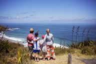 Rear view of family standing on hill and looking at sea against sky - CAVF29606