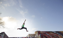 Low angle view of stunt man jumping over buildings against sky - CAVF29645