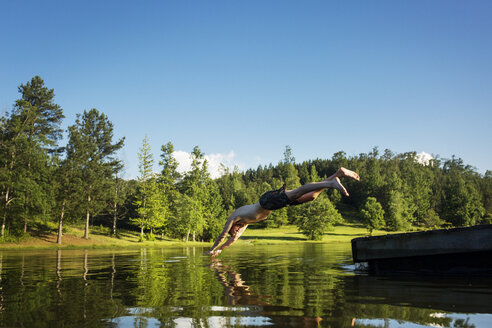 Full length of shirtless man diving into lake against clear sky - CAVF29719
