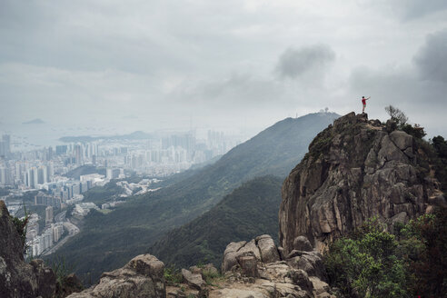 Distant view of man standing on mountain by cityscape during foggy weather - CAVF29773