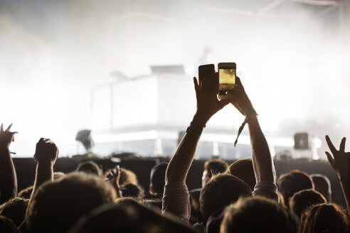 Person photographing through smart phone at music concert - CAVF29776