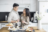 Happy couple with drinks looking at each other while standing in kitchen at home - CAVF29797