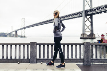 Side view of female athlete looking at Oakland Bay Bridge while standing on footpath - CAVF29809