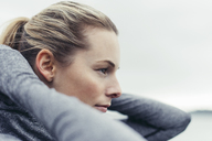 Close-up of thoughtful athletic woman wearing hooded jacket against clear sky - CAVF29815