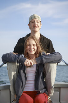 Portrait of teenage girl and young man sitting on boat - FOLF02108