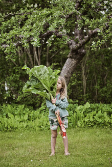 Girl standing on grass and holding large rhubarb leaves - FOLF02225