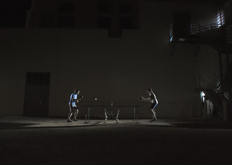 Friends playing table tennis against building at night - CAVF29896