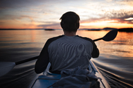 Rear view of man kayaking during sunset - CAVF30085