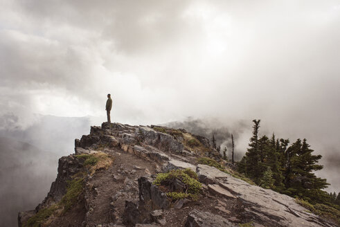 Side view of man standing on cliff against cloudy sky - CAVF30109