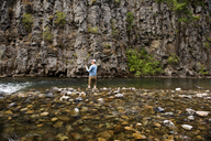 Rear view of man fly fishing at river against rock formations - CAVF30118