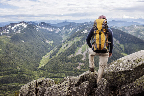 Rear view of hiker standing against mountain range - CAVF30247