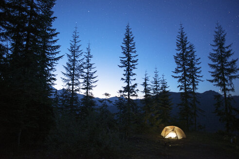 Illuminated tent on silhouette mountain at night - CAVF30283