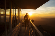 Rear view of hiker standing at fire lookout tower during sunset - CAVF30334