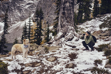 Man photographing dog in forest during winter - CAVF30340