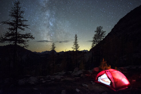 Illuminated tent on field against starry sky - CAVF30346