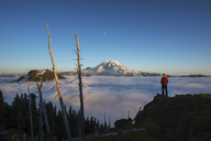 Rear view of male hiker standing on mountain by cloudscape during sunrise - CAVF30376