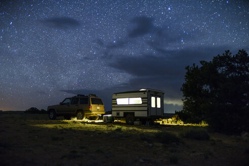 Car and illuminated travel trailer against star field - CAVF30388