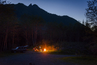 Hiker camping by campfire against mountains during dusk - CAVF30391