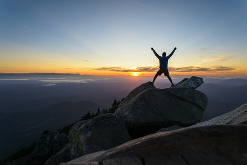 Silhouette man with arms raised standing on rocks against sky at Mount Pilchuck State Park during sunset - CAVF30407