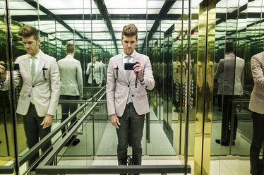 Reflection of man photographing with camera in mirror at elevator - CAVF30443