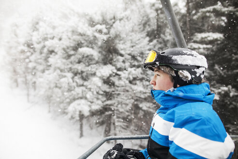 Side view of man in ski lift against snow covered trees - CAVF30536