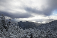 Scenic view of snow covered trees and mountains against cloudy sky - CAVF30539