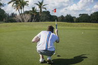 Rear view of man focusing in golf course - CAVF30566