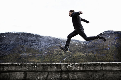 Man jumping over stone wall - FOLF02450