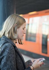 Young woman using smartphone on Helsinki Metro - FOLF02558