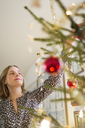 Young woman decorating Christmas tree - FOLF02567
