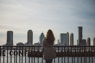 Rear view of woman looking at city skyline against clear sky - CAVF30580
