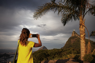 Rear view of woman photographing with smart phone against cloudy sky - CAVF30604