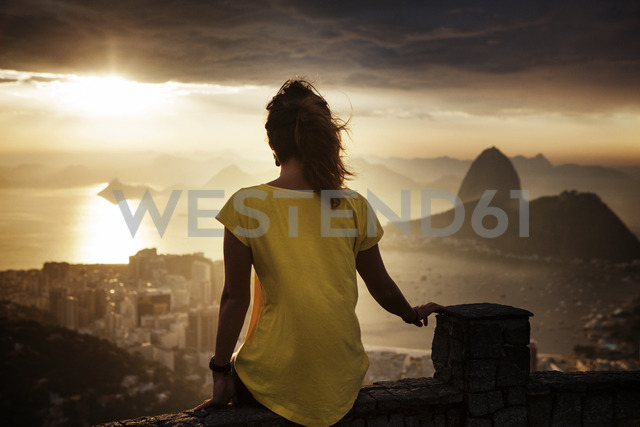 Rear view of woman sitting on retaining wall at observation point during sunset - CAVF30607