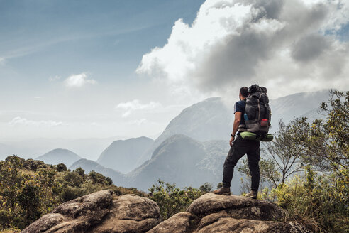 Male backpacker standing on mountain against sky - CAVF30616