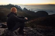 Man holding mug while sitting on mountain during sunset - CAVF30622