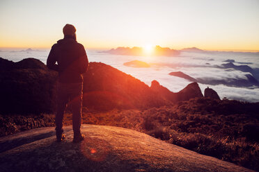 Rear view of hiker standing on mountain during sunset - CAVF30631