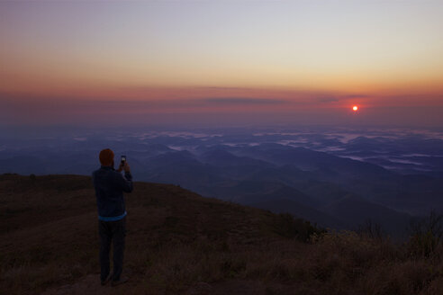 Man photographing scenic view of sunset while standing on mountain - CAVF30634