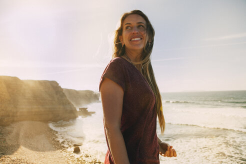 Smiling woman looking away while standing at beach against sky - CAVF30673