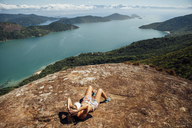 High angle view of woman relaxing on mountain by sea during sunny day - CAVF30712