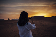Rear view of woman photographing through mobile phone at desert against cloudy sky during sunset - CAVF30718