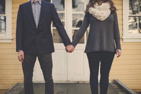 Midsection of couple holding hands while standing in front of house - CAVF30811