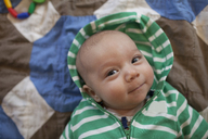 High angle portrait of cute baby boy wearing hooded shirt while lying on bed at home - CAVF30826