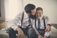 Happy bridegroom kissing pageboy while sitting on bed at home - CAVF30835