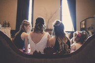 Rear view of bride sitting with bridesmaids and flower girl on sofa at home - CAVF30841