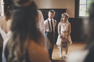 Flower girl with pageboy looking at bride during wedding ceremony - CAVF30844