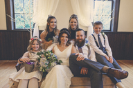 Portrait of newlywed couple sitting by pageboy and flower girl with bridesmaids on sofa during wedding ceremony - CAVF30847