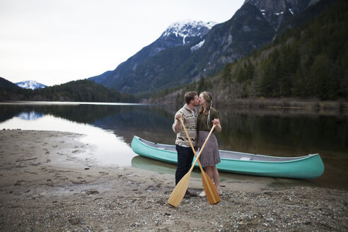 Young couple kissing while holding oars at lakeshore against mountains - CAVF30868