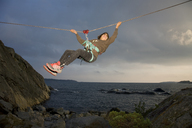 Teenage boy on tyrolean traverse at dusk - FOLF02909