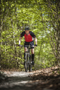 Mature man riding on mountain bike through forest - FOLF02939